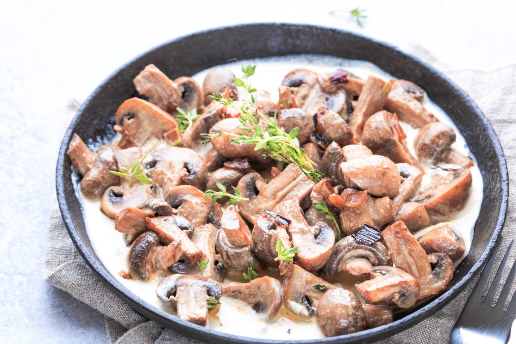 mushrooms cooking in a pan with garnish