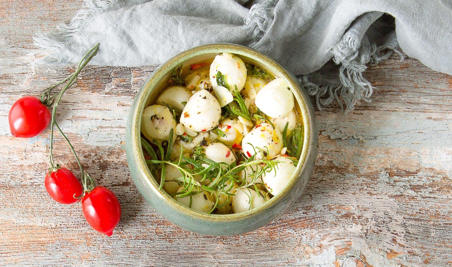 marinated mozzarella balls in a bowl with fresh veggies
