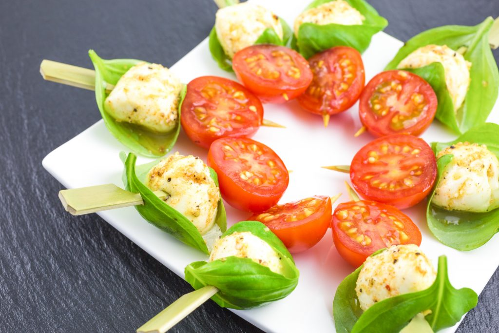 serving marinated mozzarella balls on a plate with basil leaves