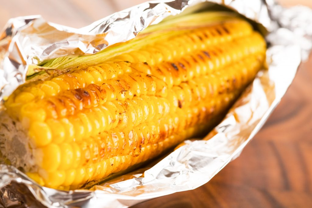 corn wrapped in tin foil for roasting