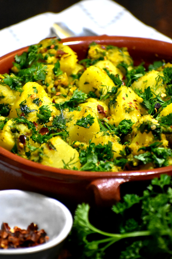 photo of Lebanese Batata Harra being served in a red bowl.