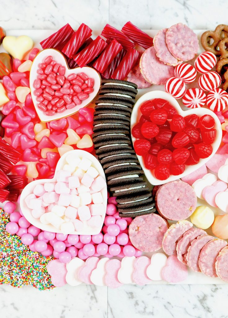 close up of a valentines day charcuterie board with cookies and candy