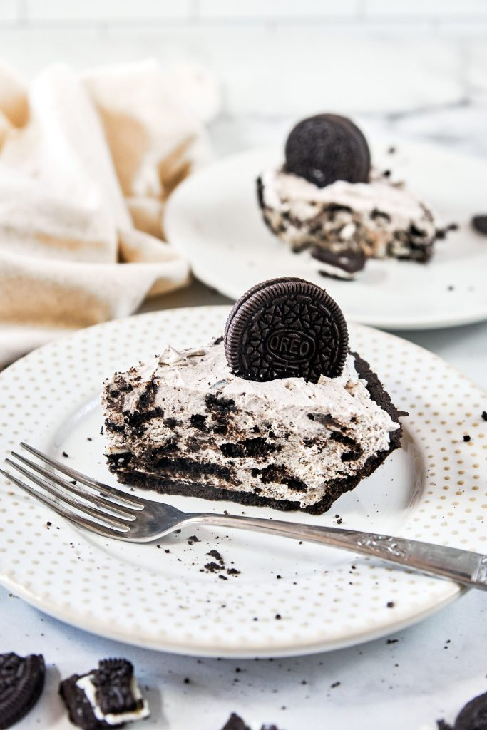 fork lying on a plate with vegan Oreo cheesecake in the background