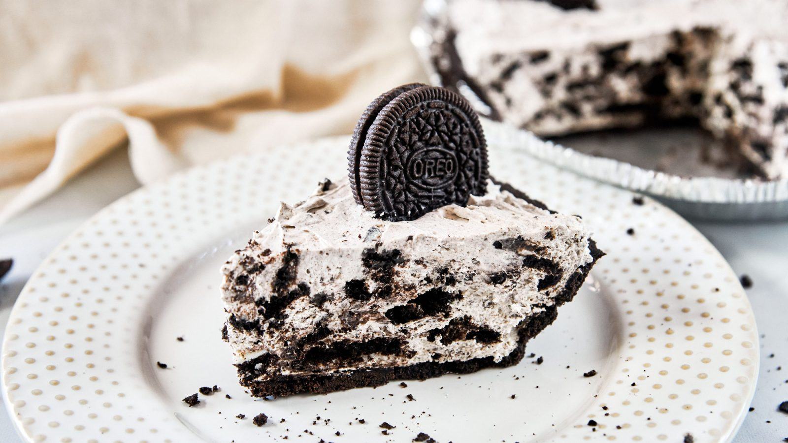 vegan Oreo cheesecake on a plate with cake in the background