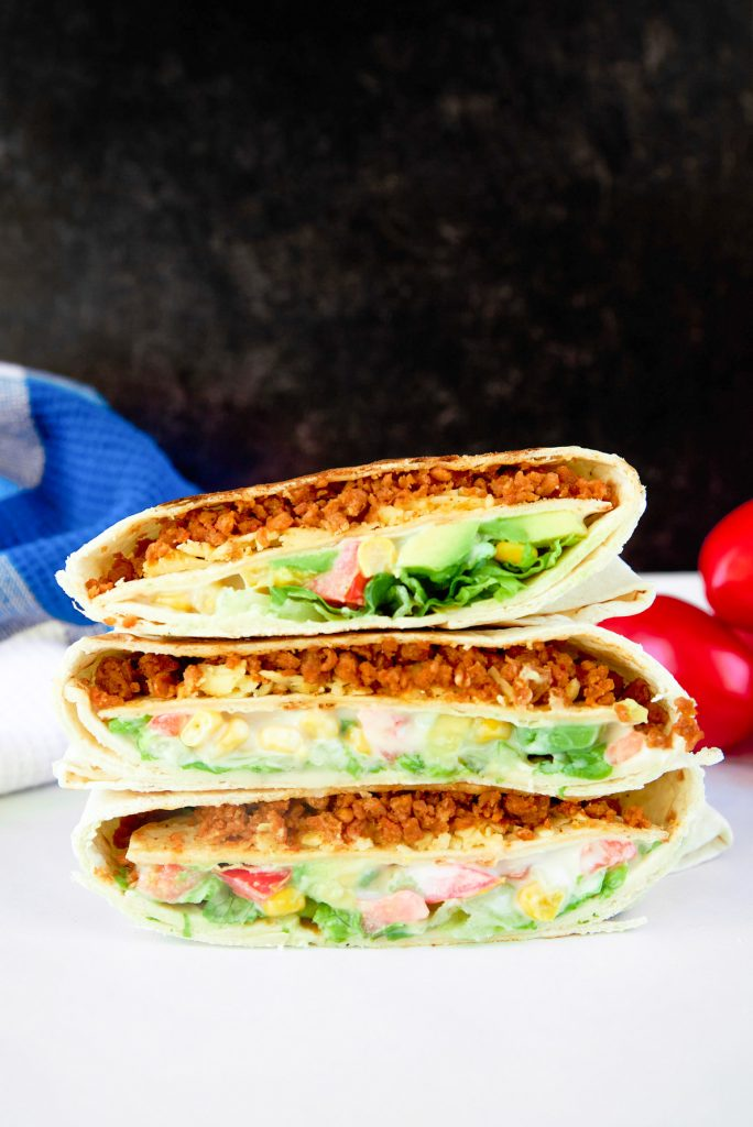 three vegan crunchwrap supremes stacked on a white counter and black background