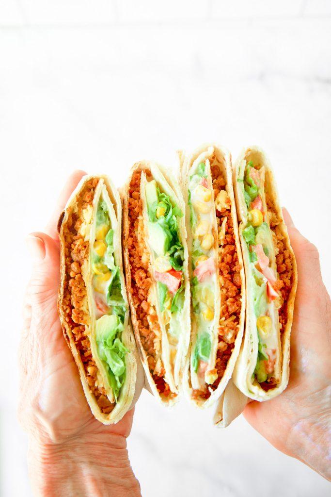 vegan crunchwrap supreme being held between hands