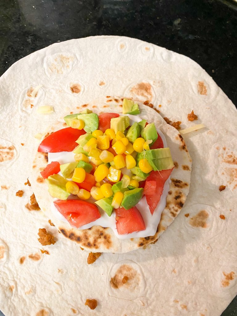 veggies on top of a tortilla with sour cream