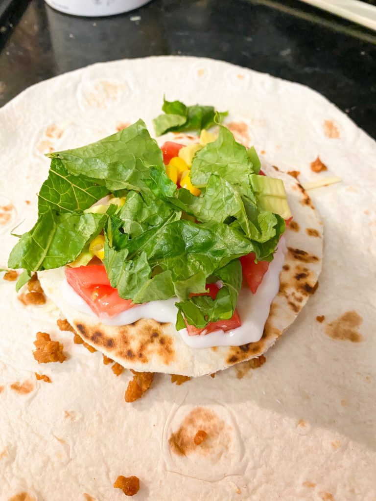shredded lettuce and veggies on top of tortillas