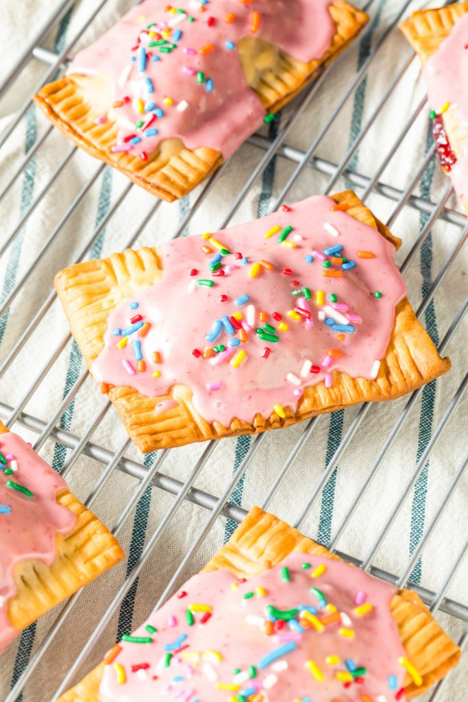 lots of vegan pop tarts on a cooling rack with dish towel
